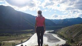 Ragazza magica che guarda alla costa del fiume della montagna da una scogliera che sembra bello paesaggio Fotografia Stock