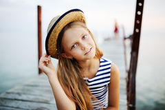 Ragazza in maglia a strisce ed in un cappello di paglia contro il mare Immagini Stock Libere da Diritti