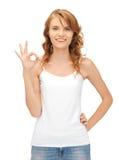 Ragazza in maglietta bianca in bianco che mostra segno giusto Immagini Stock