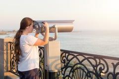 Ragazza in maglietta bianca che guarda con il binocolo a gettoni sulla riva di mare Sguardo della donna in telescopio turistico s Fotografia Stock