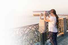 Ragazza in maglietta bianca che guarda con il binocolo a gettoni sulla riva di mare Sguardo della donna in telescopio turistico s Immagini Stock Libere da Diritti