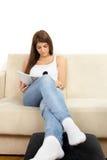 Ragazza in maglietta e jeans bianchi che legge rivista sullo strato Fotografia Stock Libera da Diritti