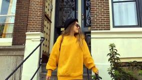 Ragazza in maglione giallo stupefacente, cappello, occhiali da sole d'uso a Amsterdam Camminata turistica, sorridendo La ragazza  archivi video