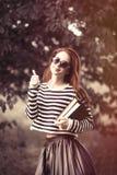 Ragazza in maglione a strisce con i libri Immagini Stock Libere da Diritti