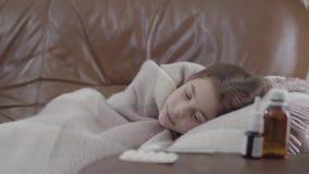 Ragazza malata adolescente del ritratto che si trova sul sofà coperto di coperta a casa, è fredda Spray nasale, pillole e sciropp video d archivio