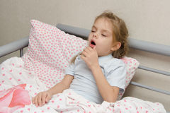 Ragazza malata che si trova a letto tossendo Immagini Stock