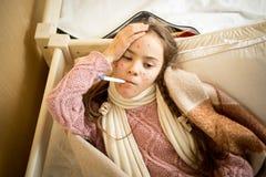 Ragazza malata con varicella che si trovano a letto e la temperatura di misurazione Fotografia Stock