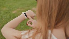 Ragazza mentre camminare nel parco tocca il touch screen di un orologio astuto Stile di vita attivo sport ricreazione stock footage