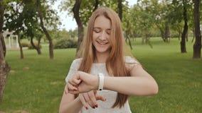 Ragazza mentre camminare nel parco tocca il touch screen di un orologio astuto Stile di vita attivo sport ricreazione archivi video