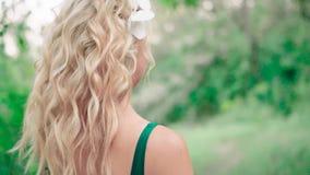 Ragazza meravigliosa con capelli biondi in una bella acconciatura riccia, supporti di nuovo alla macchina fotografica, lentamente stock footage