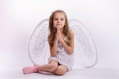 Ragazza messa con le mani piegate ali di angelo Fotografia Stock