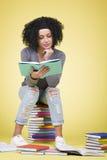 Ragazza messa a fuoco gioiosa che studia con i libri multicolori Fotografia Stock Libera da Diritti