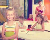 Ragazza minore sorridente che sta con il manuale a scuola Fotografia Stock Libera da Diritti