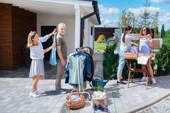 Ragazza mora che prova collana rosa luminosa mentre visitando vendita di oggetti usati con l'amico fotografie stock