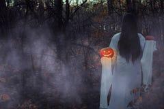 Ragazza morta con la Jack-o-lanterna in una foresta nebbiosa alla notte immagini stock