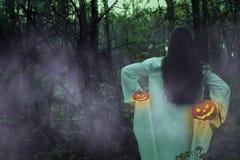Ragazza morta con la Jack-o-lanterna in una foresta nebbiosa alla notte immagine stock libera da diritti