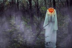 Ragazza morta con la Jack-o-lanterna in una foresta nebbiosa alla notte fotografie stock