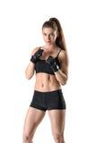 Ragazza muscolare sportiva di forma fisica che serra i suoi pugni che indossano i guanti neri nella posizione difensiva Fotografie Stock