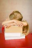 Ragazza nascosta dietro i libri del mucchio Fotografia Stock