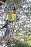 Ragazza negli ostacoli del passaggio del parco della corda, salita della ragazza la strada fotografia stock libera da diritti