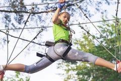 Ragazza negli ostacoli del passaggio del parco della corda, salita della ragazza la strada immagine stock