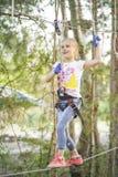Ragazza negli ostacoli del passaggio del parco della corda, salita della ragazza la strada Parco della corda fotografie stock