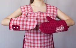 Ragazza nei guanti della cucina su fondo grigio fotografie stock libere da diritti