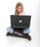 Ragazza nei suoi anni dell'adolescenza facendo uso del computer portatile Immagine Stock