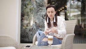 Ragazza nel caffè nell'aria fresca che si siede in un latte bevente della sedia da una tazza di vetro attraverso una paglia archivi video