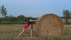 Ragazza nel campo al tramonto ed al mucchio di fieno stock footage
