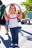 Ragazza nel campo da giuoco della scuola con il cerchio Fotografie Stock