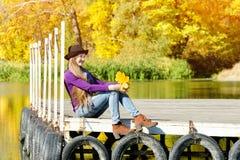 Ragazza nel cappello che si siede sul bacino dal fiume Autunno, soleggiato Fotografia Stock