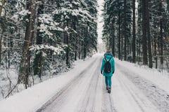 Ragazza nel cappotto blu sulla strada nell'umore allegro di inverno della foresta fredda di inverno in donne Immagine Stock