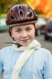 Ragazza nel casco da portare della bicicletta di caduta Immagine Stock