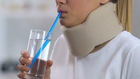 Ragazza nel disagio ritenente del collare cervicale della schiuma, supporto ortopedico, trauma video d archivio