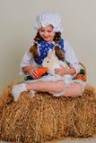 Ragazza nel fieno che alimenta le carote del coniglietto di pasqua Immagini Stock Libere da Diritti