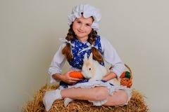 Ragazza nel fieno che alimenta le carote del coniglietto di pasqua Immagine Stock