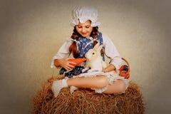 Ragazza nel fieno che alimenta le carote del coniglietto di pasqua Fotografia Stock
