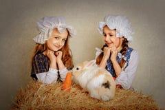 Ragazza nel fieno che alimenta le carote del coniglietto di pasqua Immagine Stock Libera da Diritti