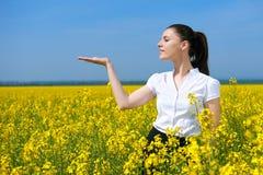 Ragazza nel giacimento di fiore giallo Mostri la palma Tenga in palma di qualcosa e sorrida Bello paesaggio della molla, giorno s Immagini Stock