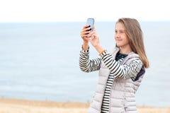 Ragazza nel giacimento di grano che prende immagine dallo smartphone Fotografie Stock