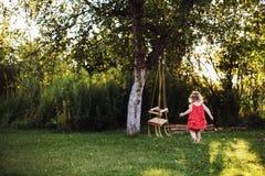 Ragazza nel giardino che gioca con le oscillazioni immagini stock