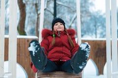 Ragazza nel giro di inverno su un'oscillazione fotografia stock