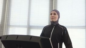 Ragazza nel hijab, riscaldamento di camminata nella fine della palestra su archivi video