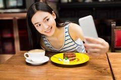 Ragazza nel negozio del caffè che manda un sms sullo smartphone Immagini Stock Libere da Diritti
