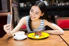 Ragazza nel negozio del caffè che manda un sms sullo smartphone Fotografie Stock Libere da Diritti