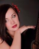 Ragazza nel nero con il fiore e la chitarra rossi Fotografie Stock