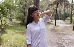 Ragazza nel parco che sta sui precedenti della foresta immagini stock libere da diritti