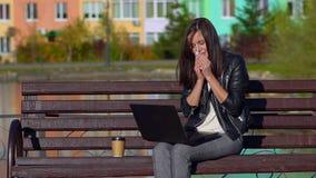 Ragazza nel parco su un banco, lavorante in un computer portatile Ha il raffreddore, pulisce il suo naso con un fazzoletto video d archivio