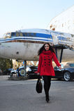 Ragazza nel rosso su un fondo di vecchio aeroplano Fotografie Stock